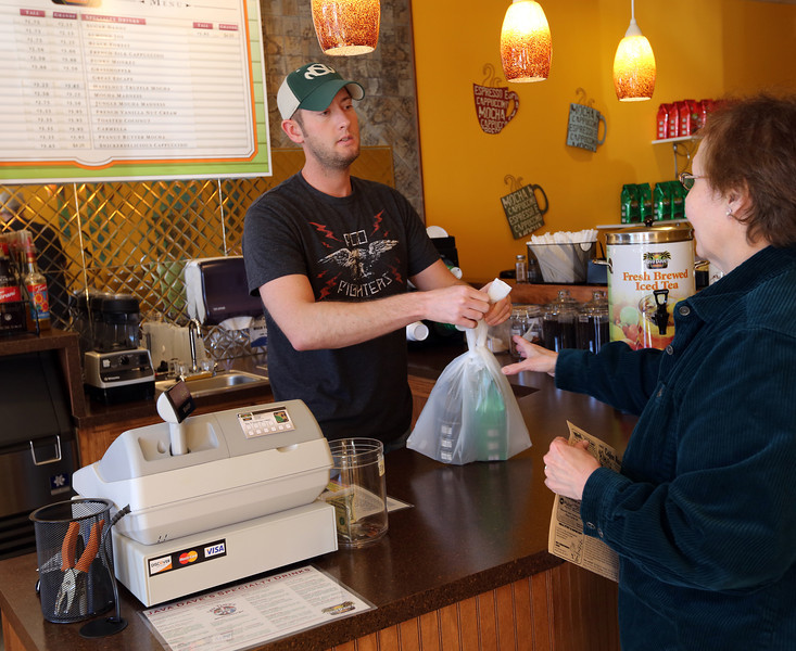 Nathan Johnston, Owner of the Java Daves coffee shop in south Tulsa, bags up a customers purchase.