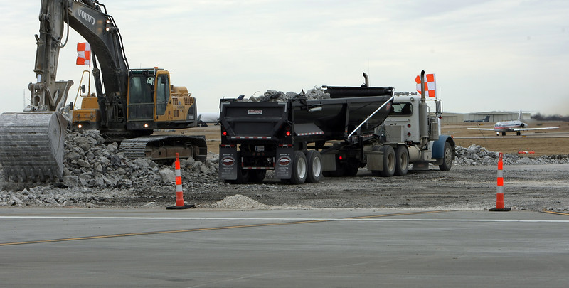 Workmen remove part of the main runway at Tulsa International Airport.