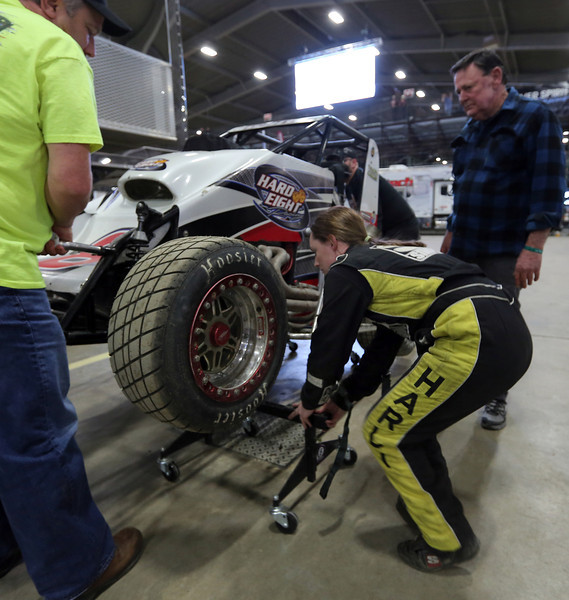 Harli White helps her crew service her car between heats  at the Chili Bowl races in Tulsa.