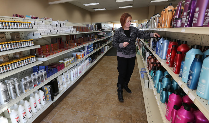 Tara Reed labels products for sale as she readies the State Beauty Supply in Claremore for customers.
