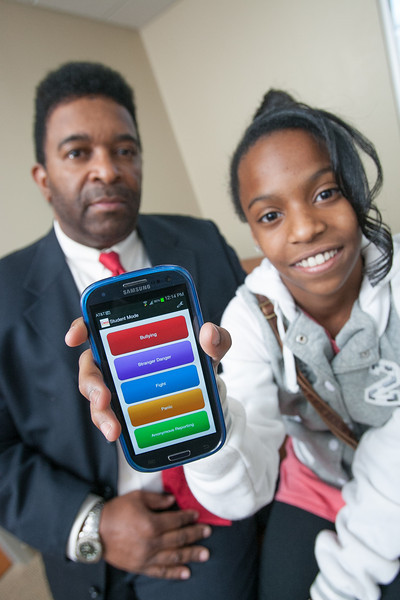 "Leonard Frank with his daughter Genisis showing their new phone app, ""Quick Response"""
