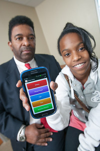 """Leonard Frank with his daughter Genisis showing their new phone app, """"Quick Response"""""""