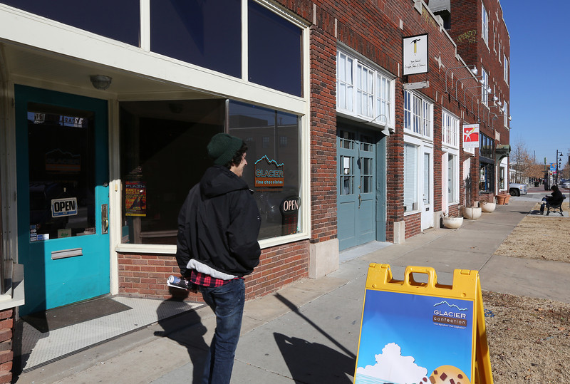A pedestrian strolls past small shops in the Brady Arts District in Tulsa.  A majority of Oklahoma entrepreneurs responding to an online survey said they had higher revenues during the last half of 2013 and expect even higher revenues in the first half of this year. The survey was operated by the Entrepreneurs' Organization, included 44 Oklahoma companies with at least $1 million in annual revenue.