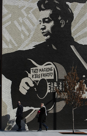 A couple walks past a mural painting on the side of the Woody Guthrie Center in Tulsa's Brady District.