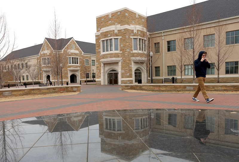 Reflected in a fountain at the Sampson Plaza Tulsa University students cross campus between classes Monday.