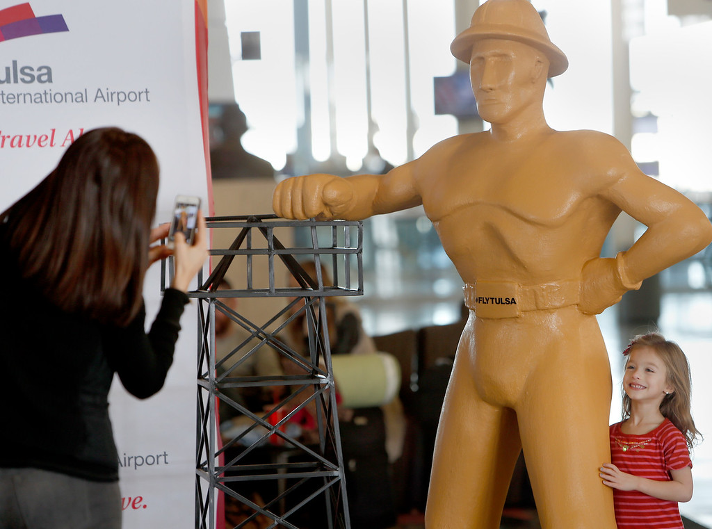 Nicole Linn shoot a photo of her daughter Eliana who is posing with a six foot tall  replica of the Golden Driller on  display at the Tulsa International Airport.