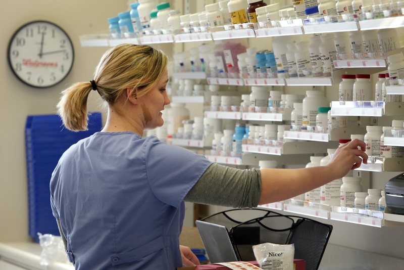 Walgreens Senior Technician Amber Frost stocks the shelves in preparation of the opening of the drug store in the Oklahoma State University Physicians building in Tulsa.