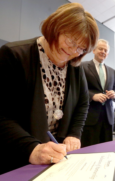 Pat McCelvey, GM of Newfield Exploration looks on as Anita Schroeder, Principle of Clark Elementary school in Tulsa signs documents forming a partnership with the company.