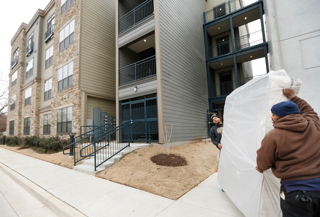 Workmen deliver a bedroom suite to the Enclave Apartments in Tulsa.