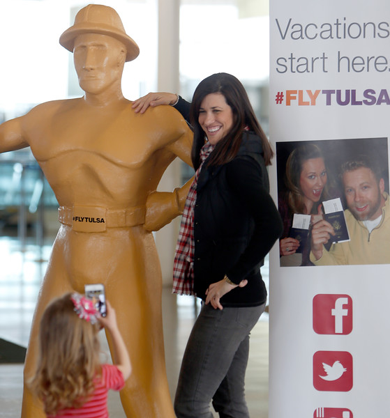 Nicole Linn poses for her daughter Eliana who is photographing her next to a six foot tall replica of the Golden Driller on  display at the Tulsa International Airport.