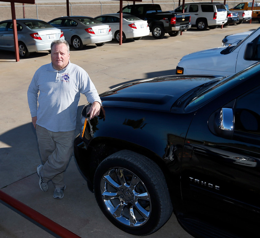 Russ Casey, President to Morris Auto Sales, pauses for a photo on his car lot.