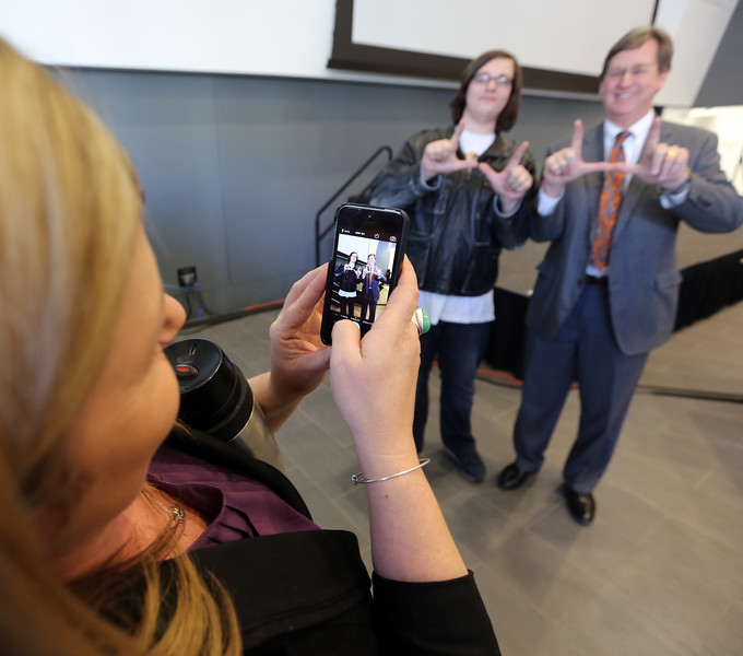 Amanda Howell uses her cell phone to capture a photo of Adam Hugely and Tulsa Mayor Dewey Bartlett after the STEM mentoring to the Max meeting in Tulsa Tuesday morning.