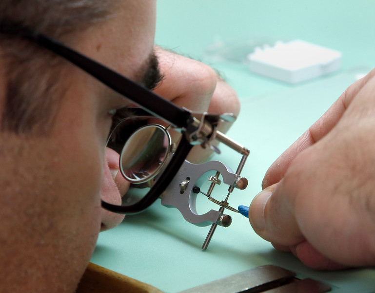 Oklahoma State University Institute of Technology watchmaking student Ryan Jewell uses a loupe and tweezers to work on a project in class.