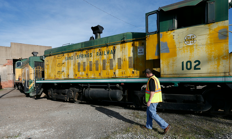 Jim Foster inspects a locomotive at the Sand Springs Railway yard before it departs Tuesday.