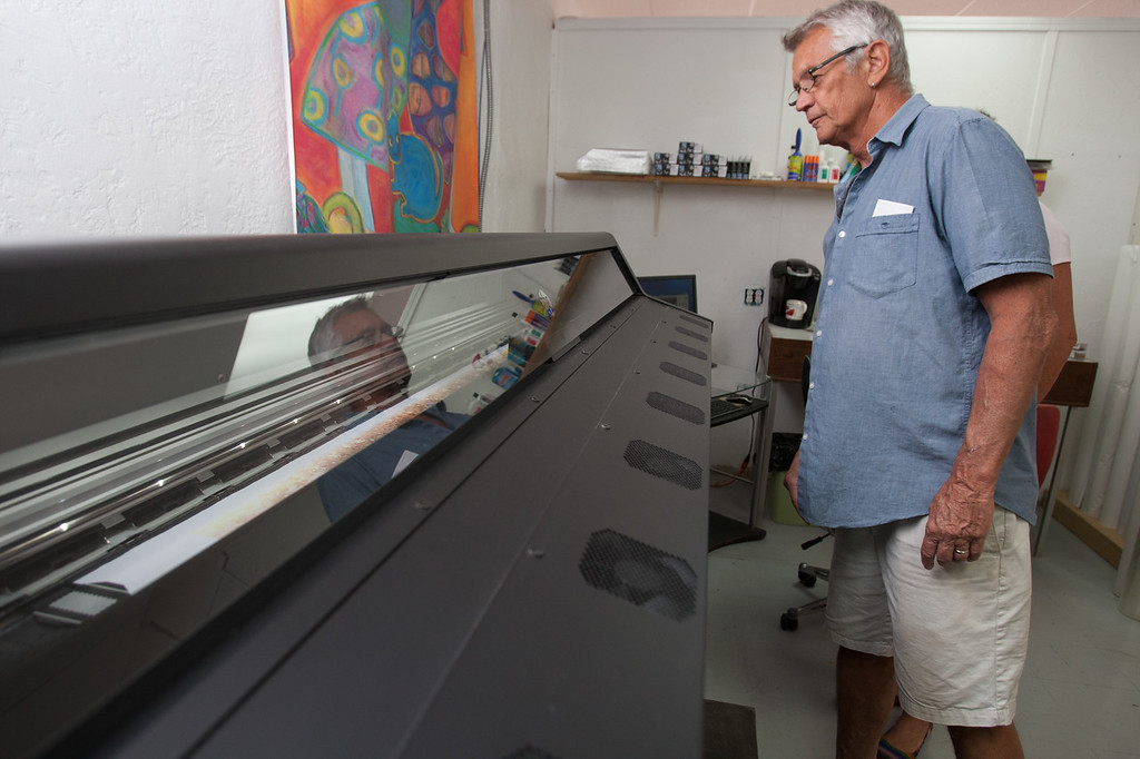 Leighton Kirkpatrick, owner of Red River Photo, with their new latex printer. The printer produces less waste and allows them to print orders such as custom wall paper.