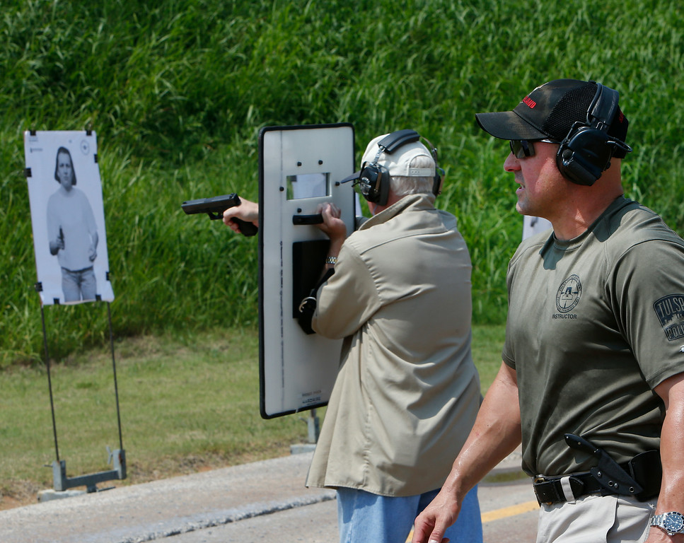 Tulsa Police range master, sergeant Brian Hill, provides instruction  to his students on shooting from behind a riot shield.