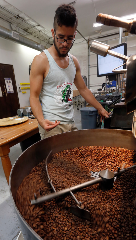 Topecca Coffee's chief roaster Jesse Jordan inspects a batch of beans being at the companies downtown Tulsa factory.