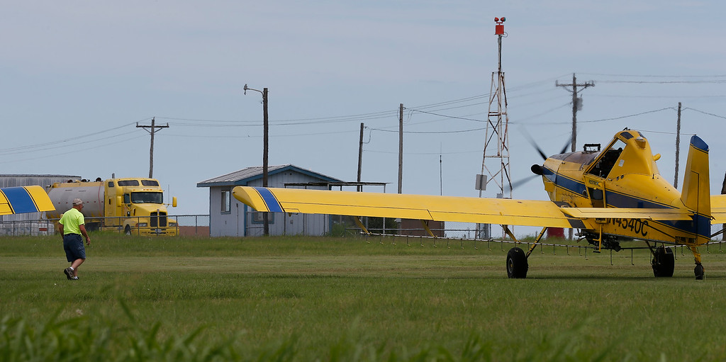 A pilot inspects his aircraft before departing on another spraying run in Osage county.