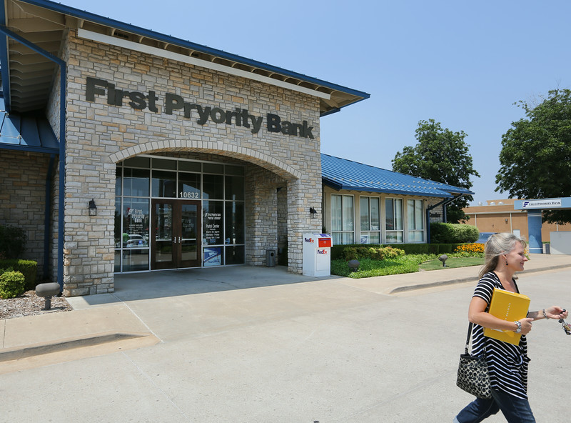 A customer exits the First Pryority Bank in Bixby.  The bank location has a a postal service center.