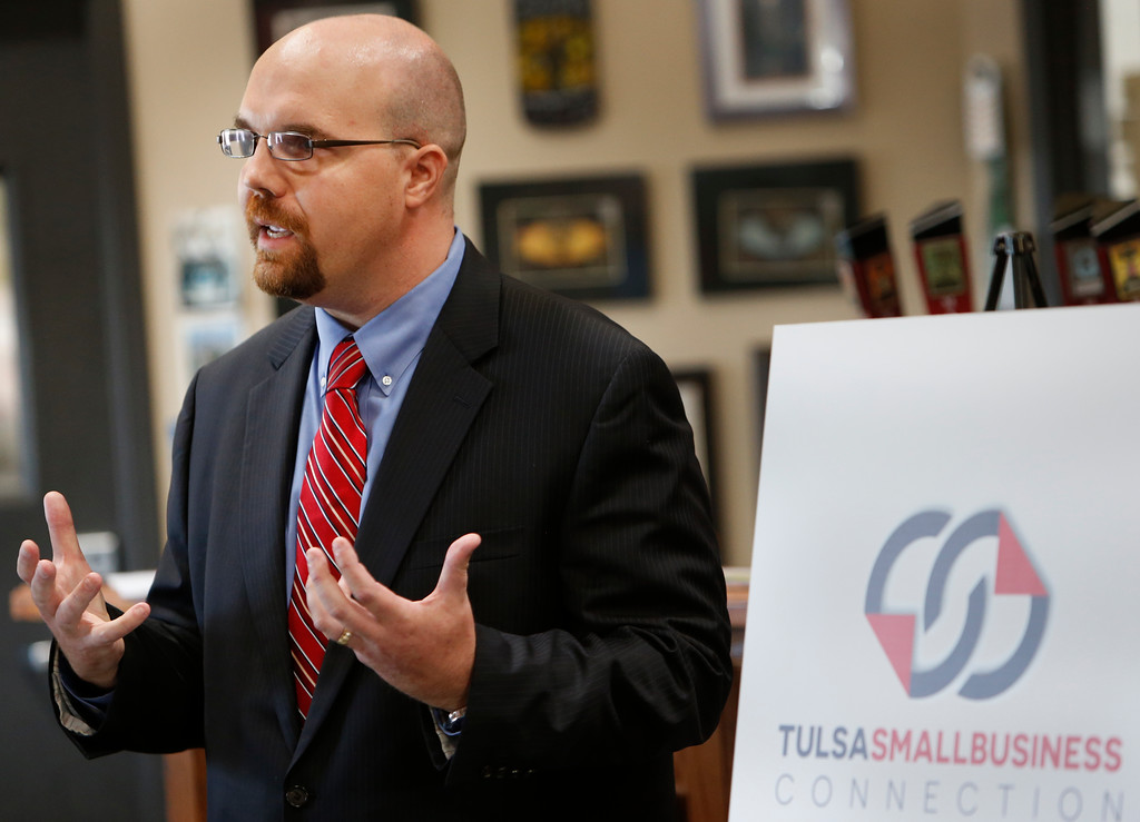 Adam Marshall, co-founder of Tulsa's Marshall Brewing and the incoming 2015 chair of Tulsa Small Business Connection gestures while giving an overview of the new program.