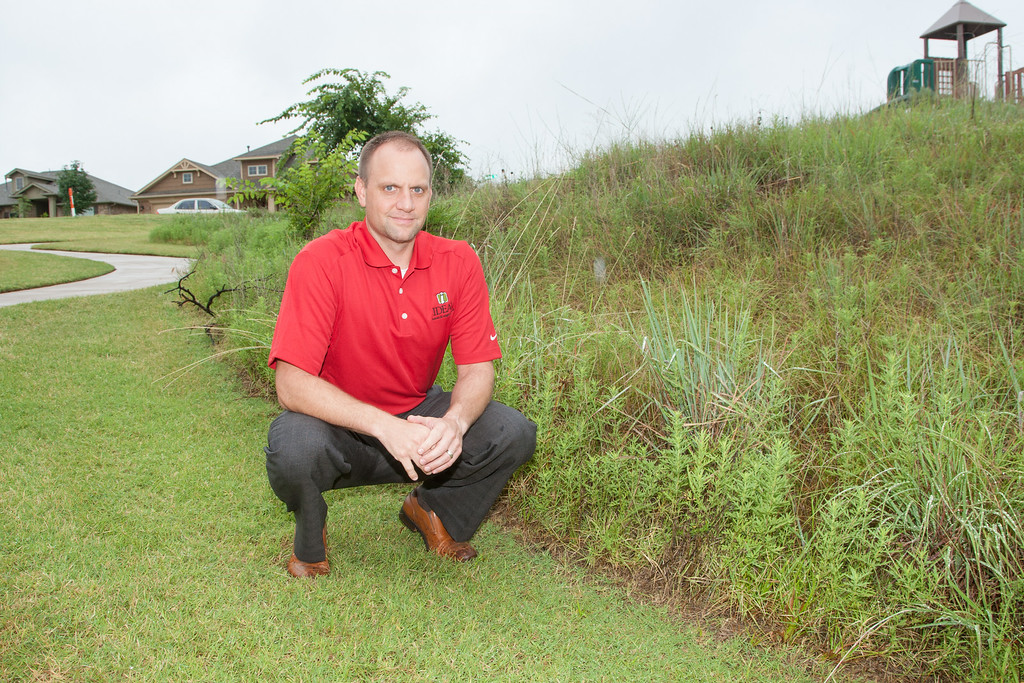 Steve Shoemaker, vice president of marketing and sales at Ideal Homes, shows a natural green space the company built into its Red Canyon Ranch development. The trees and native grasses help filter out pollution from neighborhoods, preventing it from entering Lake Thunderbird. Photo by Brent Fuchs.