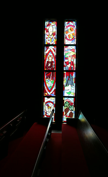 Stained glass windows are reflected in the pews at the John Calvin Presbyterian Church in east Tulsa.