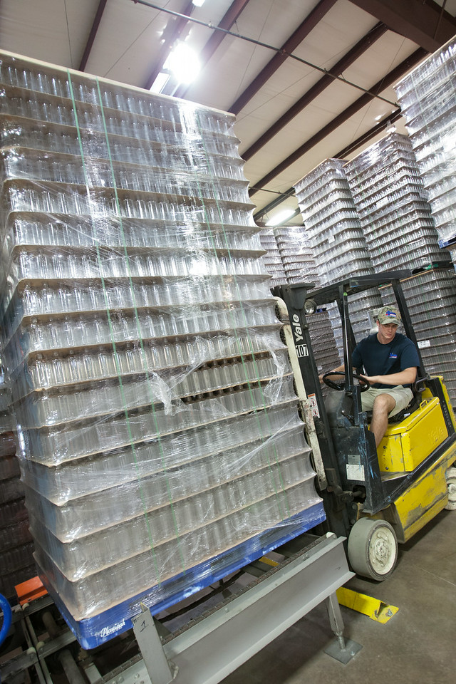 A palet of empty Ozarka Water bottle being placed at the begining of a convayer system that will wash, fill and lable each container.