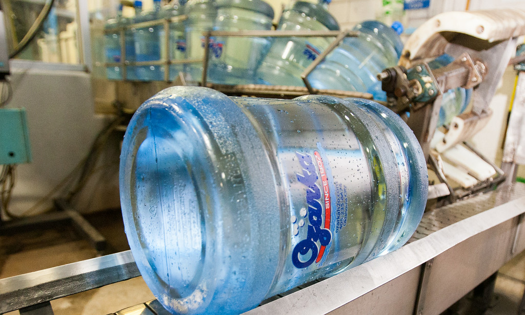 A five gallon Ozarka Water jug coming off the convayer system that washes and refills the containers after use.