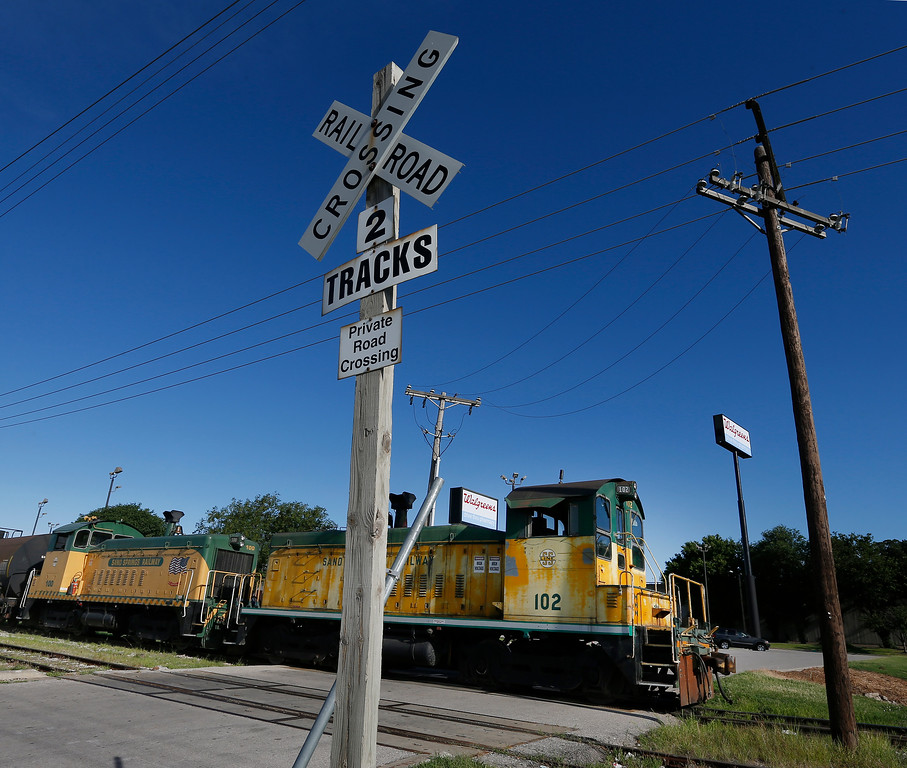 A locomotive of the Sand Springs Railway crosses an intersection while transporting freight to downtown Tulsa.