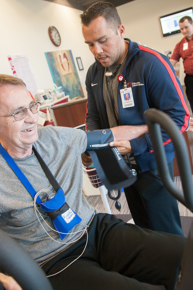 Patient Stephen Kennedy rides a stationary bicycle as part of his weekly cardiac rehabilitation at Oklahoma Heart Hospital's South Campus. Sam Jeffcoat, manager of outpatient and inpatient cardiac rehab, takes Kennedy's vitals during his workout. Photo by Brent Fuchs.