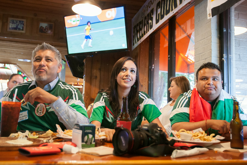 Jorge Hernadez, Marisol Espinoza and Omar Zamudio watching the World Cup at a watch party hosted by The Oklahoma City Hispanic Chamber of Commerce at Hooters on I-240 in Oklahoma CIty.