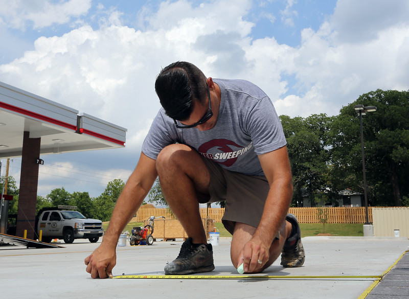 Sooner Sweeping owner Gene Terronez, measures out parking spaces for a new Quik Trip store in south Tulsa.