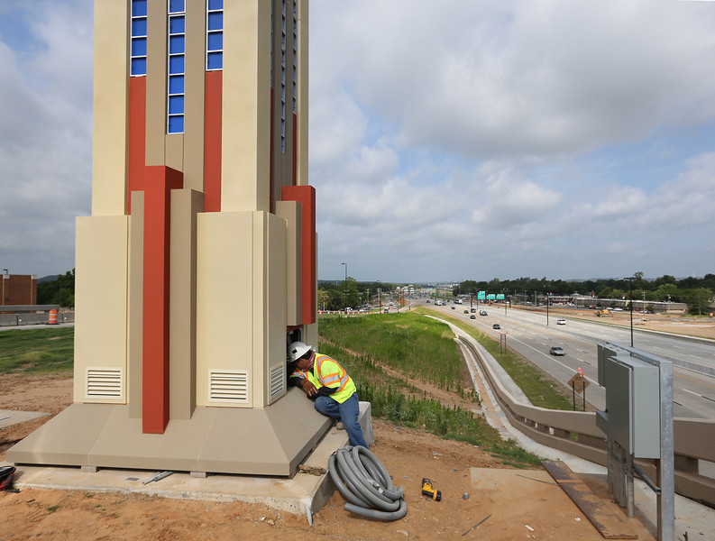 A workman puts some finishing touches on one of the six 30-foot towers erected as part of the art deco theme along the new I-44 corridor between Lewis Avenue and Riverside Drive in Tulsa.