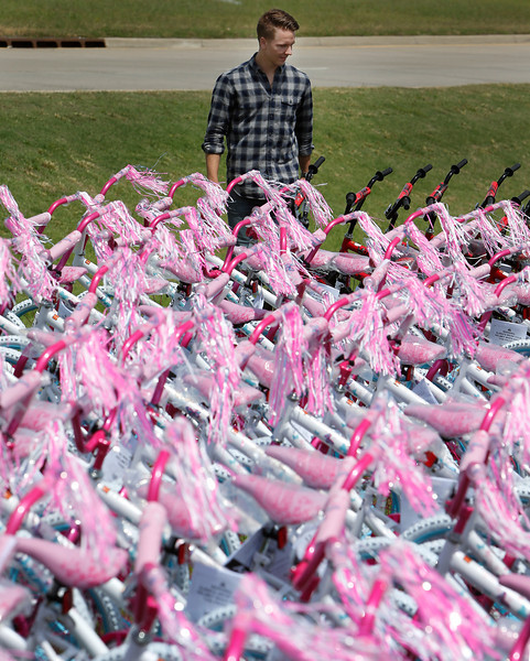 "Joshua Tygart walks past a section of the 1000 bicycles that will be given away to any child that attends the Friday Groceries rally June 6th at OneOk field in Tulsa. Guts Church in Tulsa along with local business owners and churches from around the area are rallying together to distribute 10,000 bags of groceries, medical and dental, legal assistance and lunch in addition to the bicycles to anyone who attends.<br /> <br /> <a href=""http://gutschurch.com/friday-groceries-june-6-2014"">http://gutschurch.com/friday-groceries-june-6-2014</a>"