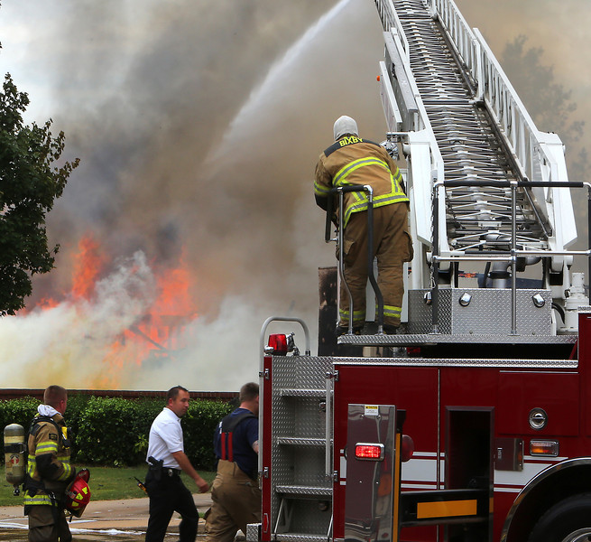 Firefighters battle a fire that destroyed the golf cart/maintenance building fire at The Link Apartments in Bixby.