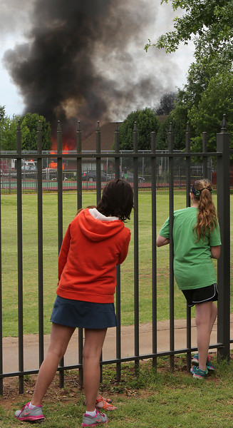 Onlookers watch as the golf cart/maintenance building at The Link Apartments in Bixby is destroyed by fire.