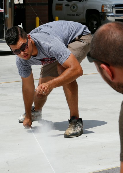 Sooner Sweeping owner Gene Terronez, marks out parking spaces for a new Quik Trip store in south Tulsa.