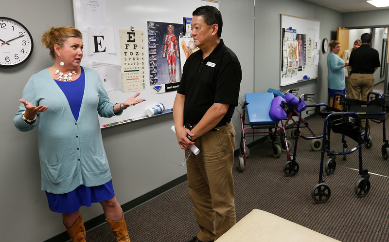Physical Therapist Keith Khoo and Audiologist Jacque Scholl chat at her Midtown Tulsa Clinic.