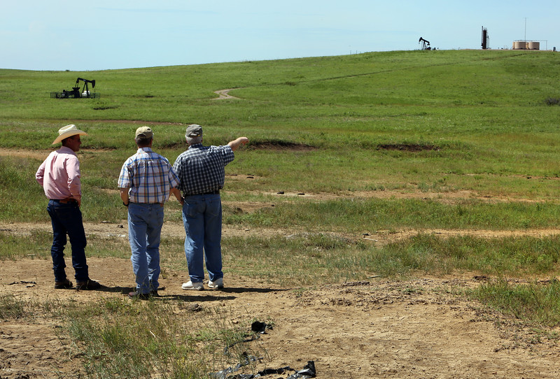 While standing in a salt brine damaged area Kerry Sublette, Sarkeys Professor of Environmental Engineering at the University of Tulsa (Right), discusses with John Hurd, Osage County Cattlemen's Association's chairman and Bob Hamilton, director of the Tallgrass Prairie Preserve the damage done by several oil and salt water spills on a lease within the Tall Grass Prairie.