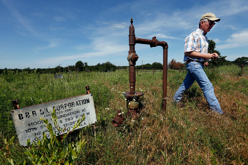 Bob Hamilton, Director of the Tallgrass Prairie Preserve  walks past oil filed equipment in Osasge County.