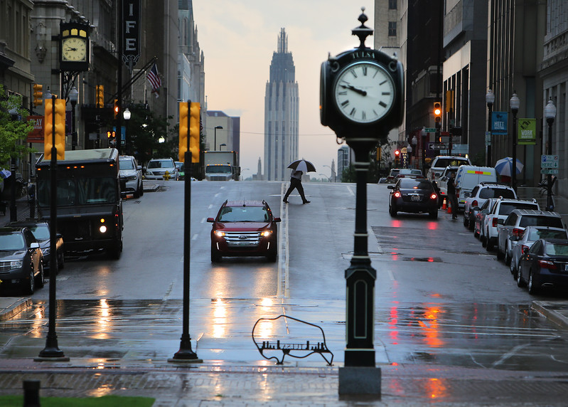Using an umbrella for shelter from early morning rain a pedestrian crosses the street in downtown Tulsa.
