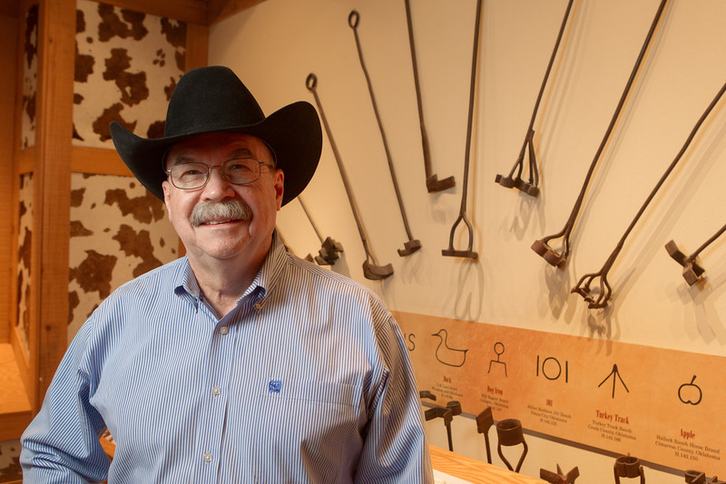 Don Reeves, curator for the National Cowboy and Western Hearitage Museum in Oklahoma City, stands in front of a collection of branding irons.