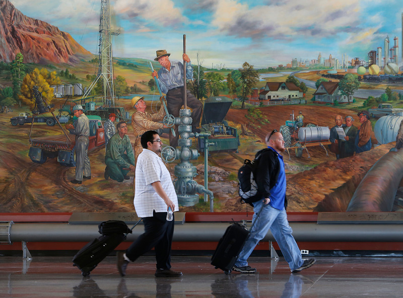 Travelers walk past a large mural at the Tulsa International Airport.