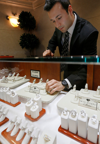 Chris Price, Director of e-commerce at Tulsa's Israel Diamond Supply, restocks the display case.