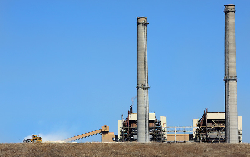 A bulldozer working on the crest of a hill is dwarfed by the smoke stacks at the coal fired electrical generation plant in Chouteau.