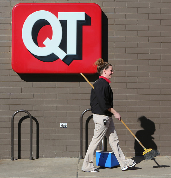 After sweeping up outside a south Tulsa QuikTrip store employee Heather Power walks back inside.