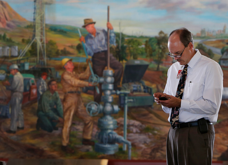 XXXX (Ray knows this guy and will provide ID)  checks his phone in front of a large mural at the Tulsa International Airport.