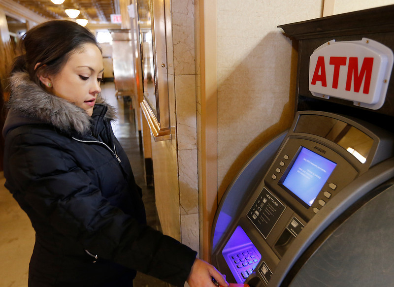 Sara Linn, Director of Sale a the Courtyard by Marriott in Tulsa, withdrawals money at the ATM in the hotels lobby.
