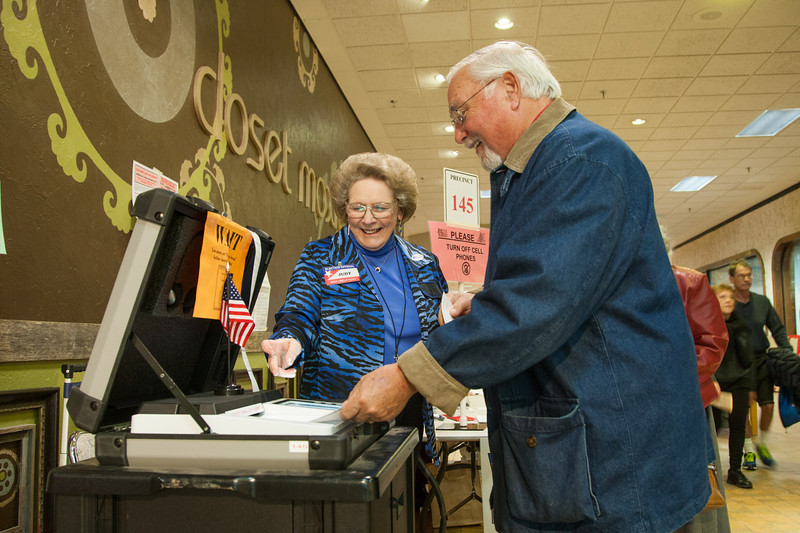 Poll worker Judy Greider helps voters scan their ballots at Northpark Mall during the 2014 mayoral elections in Oklahoma CIty, OK.