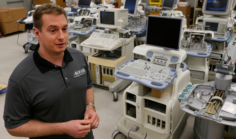John Hiryshchuck, President of Advanced Ultrasonic Electronics walks among the many machines being repaired at his Tulsa company.
